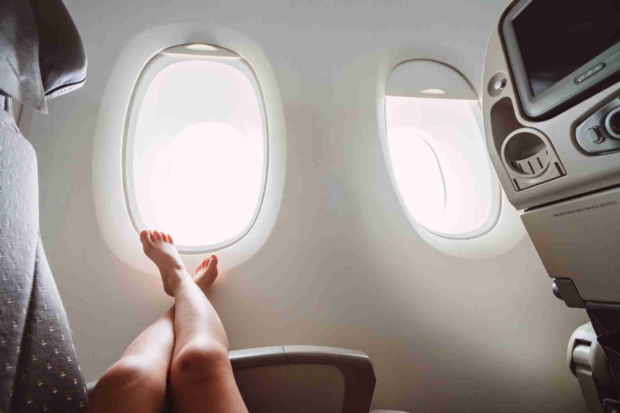 Little girl relaxing and putting her feet on the arm rest lying down on the seat in the aircraft cabin