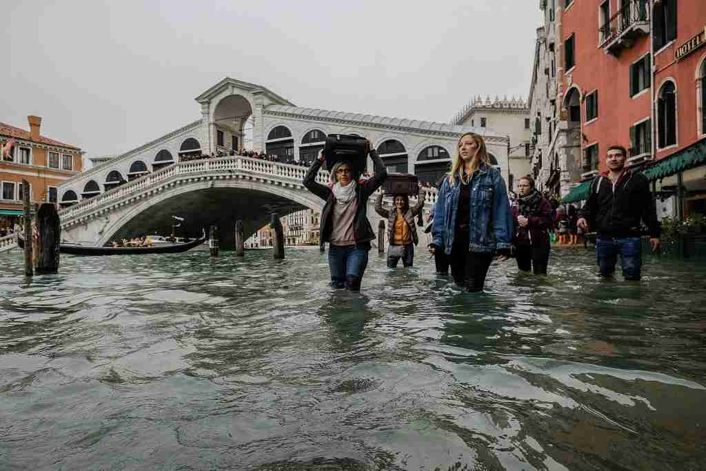 "VENICE, ITALY - OCTOBER 29: A tourist walks with his luggage near Rialto bridge on October 29, 2018 in Venice, Italy. Today due to the exceptional level of the ""acqua alta"" that reaced 156 cm schools and hospitals of Venice remained closed the authorities have also advised citizens against leaving their homes (Photo by Stefano Mazzola/Awakening/Getty Images)"