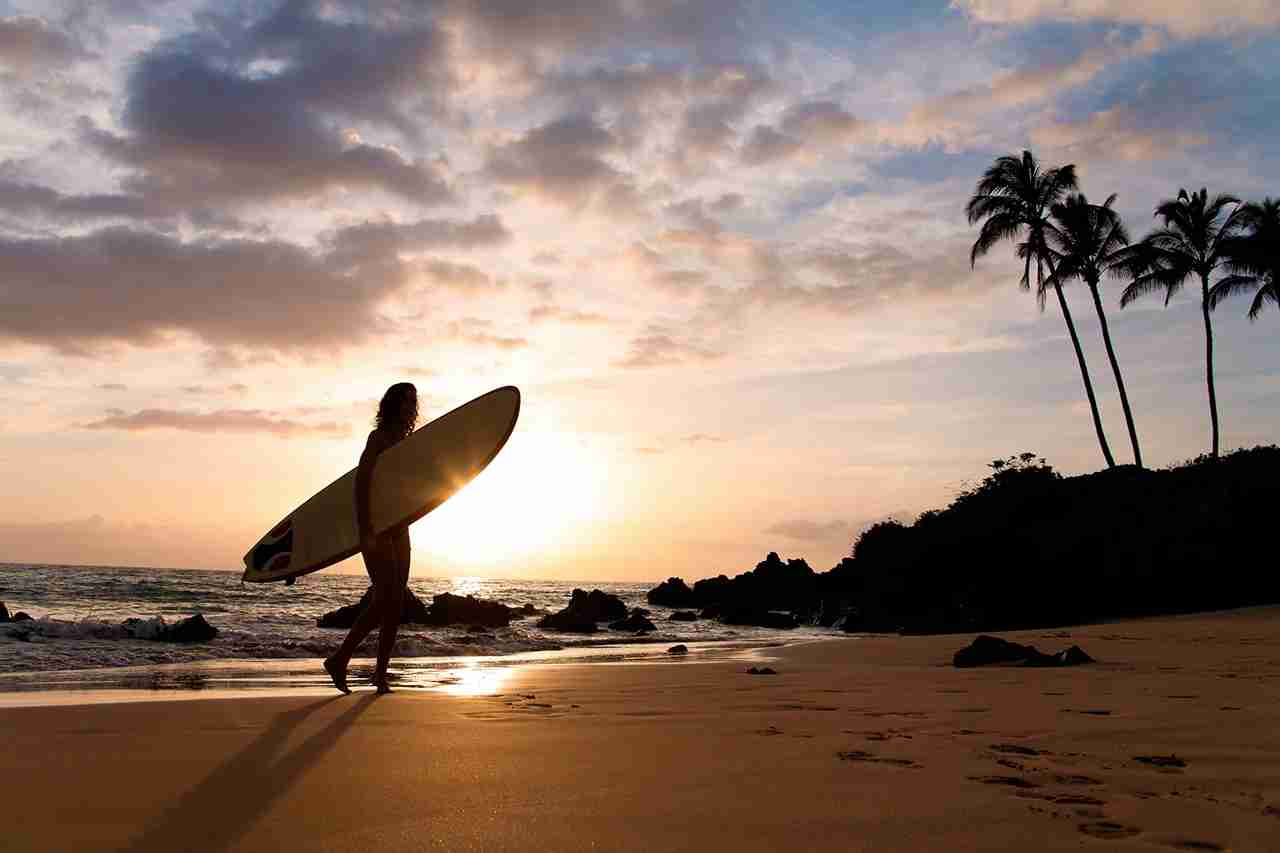 Surfer at silhouette in sunset on tropical beach in Maui, Hawaii.