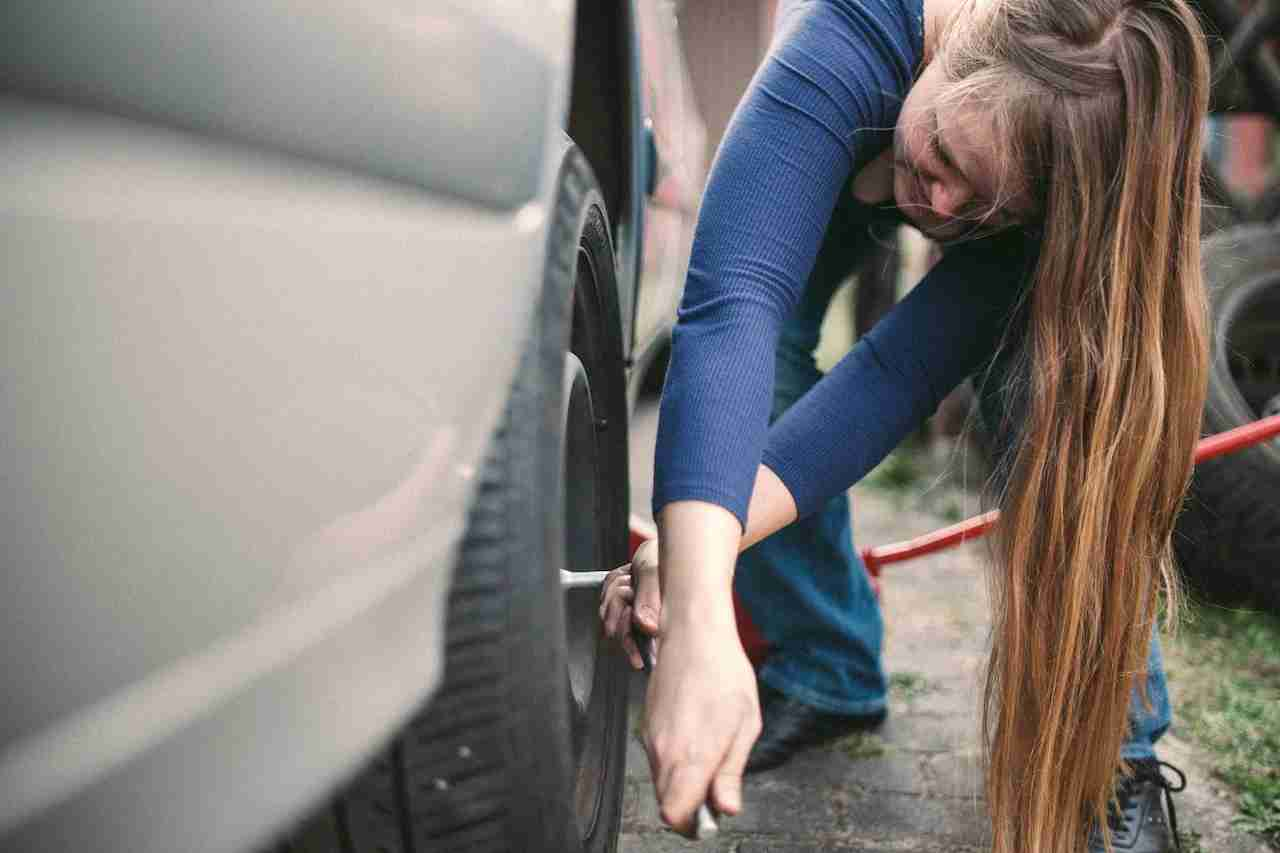 Blondhaired woman changing a car tire.