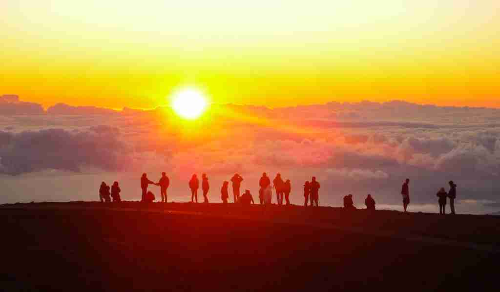 Tourists watch the sunset from the summit of Haleakala on Maui. (Photo by Xuan Che/Getty Images)