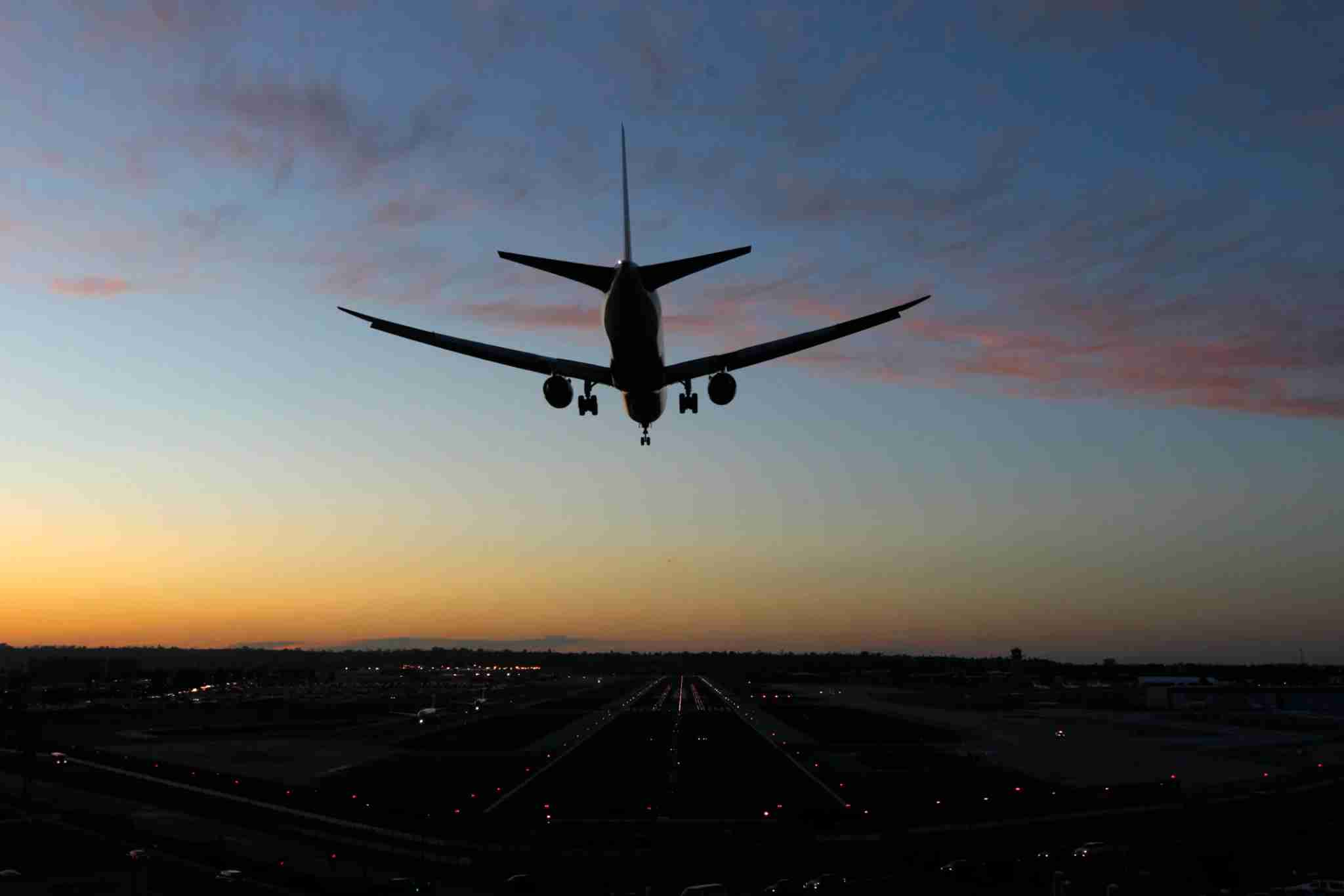 A 787 jet airplane lands at San Diego International Airport at sunset.