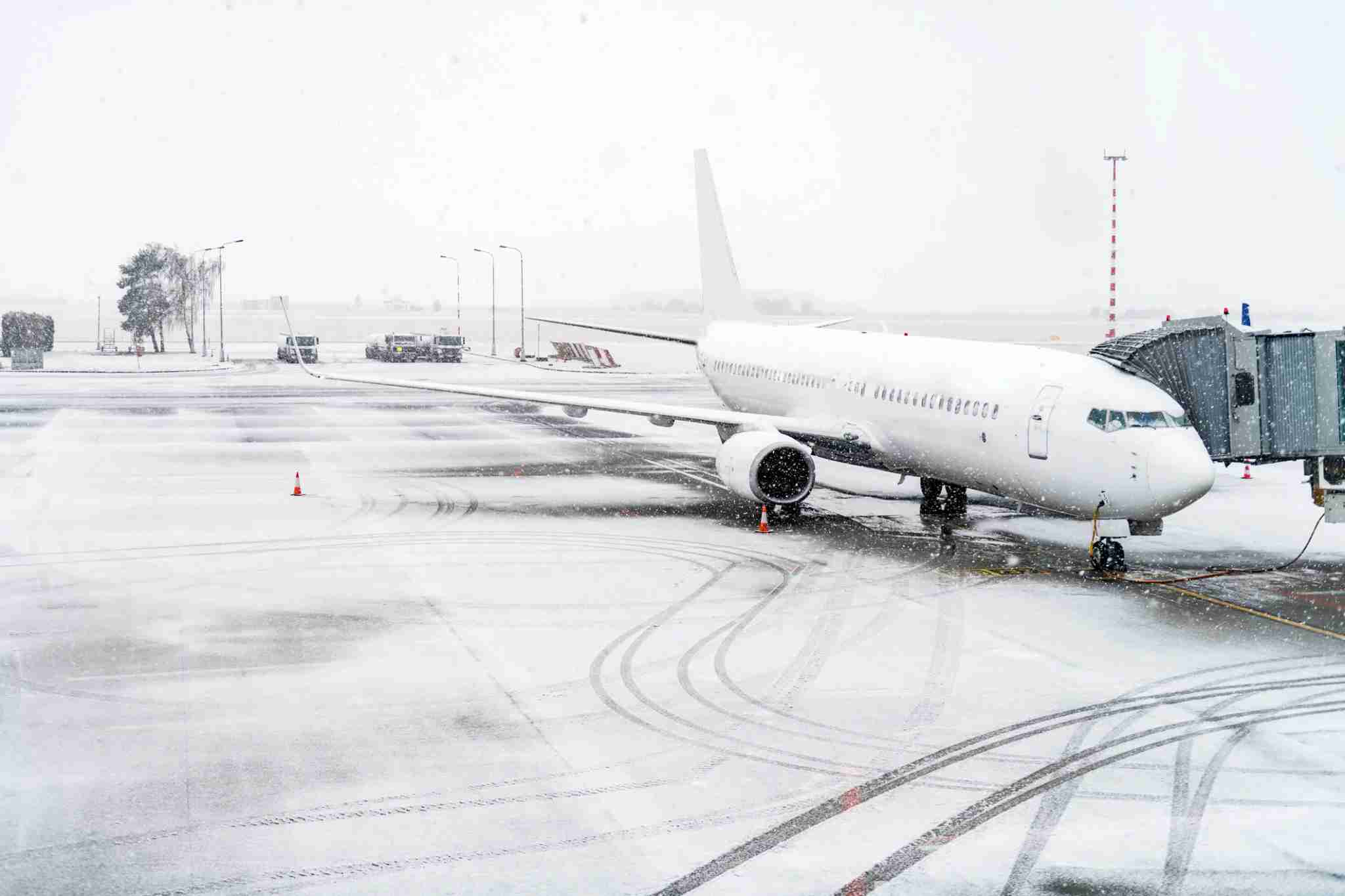 Horizontal color image of airplane during snowstorm.