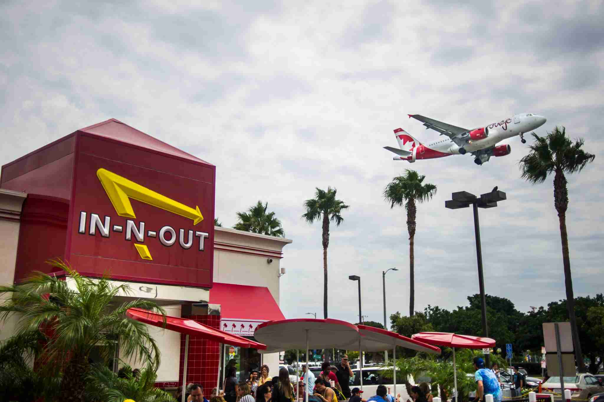 LOS ANGELES, CA - AUGUST 02: An Air Canada Rouge flight is seen above the In-N-Out Burger restaurant Sepulveda Boulevard arriving at Los Angeles International Airport on Saturday, August 02, 2014 in Los Angeles, California. More than 1,500 flights depart and arrive at LAX on a daily basis, ranking it 6th busiest in the world, and 2nd busiest in the United States. (Photo by Kent Nishimura/The Denver Post via Getty Images)