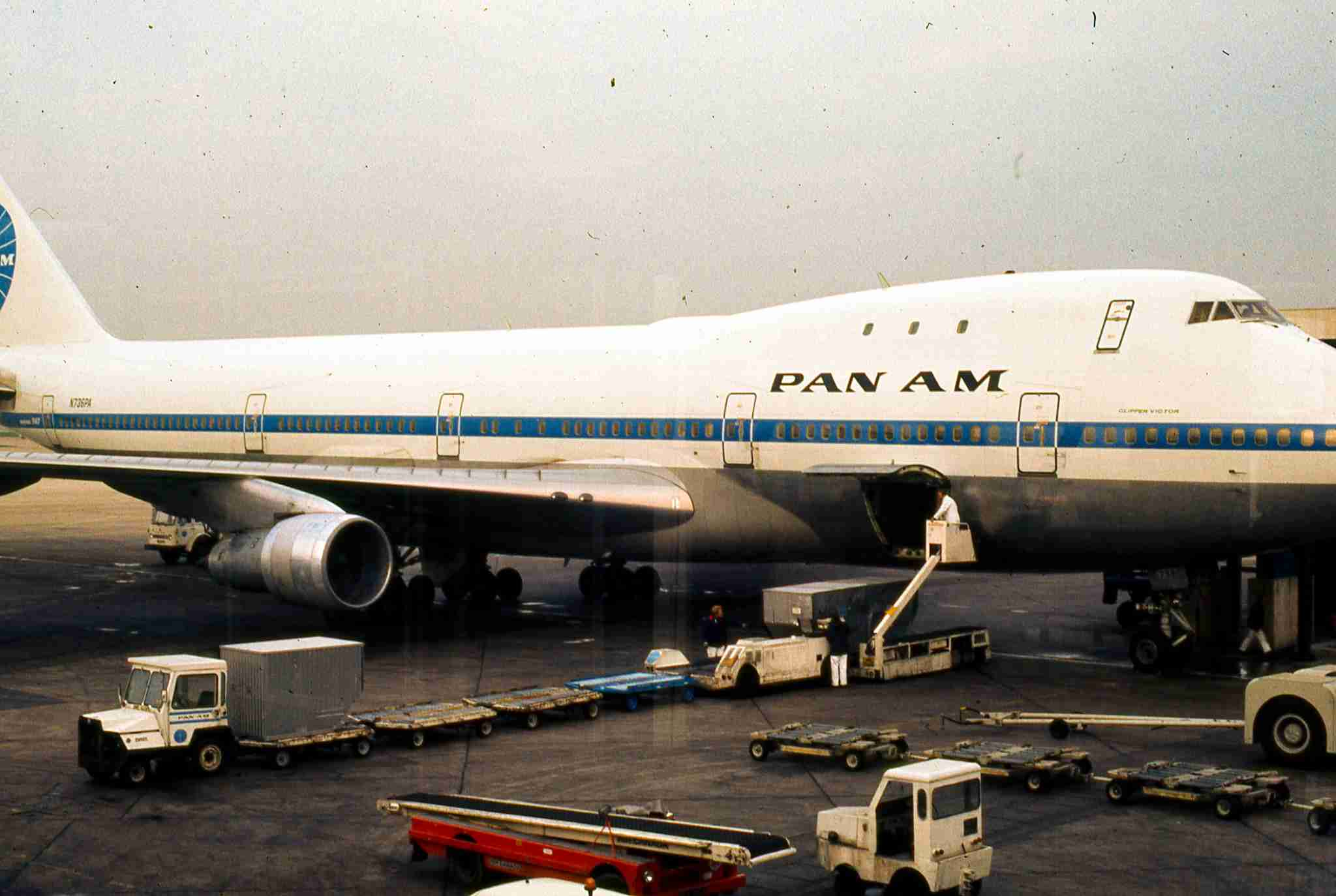 "Portrait of the ""Clipper Victor"", a Pan American World Airways 747 jet airplane parked at its terminal gate at Heathrow Airport, outside London, England, November, 1973. Baggage handlers wait with their idling luggage carrier trucks below the airplane"