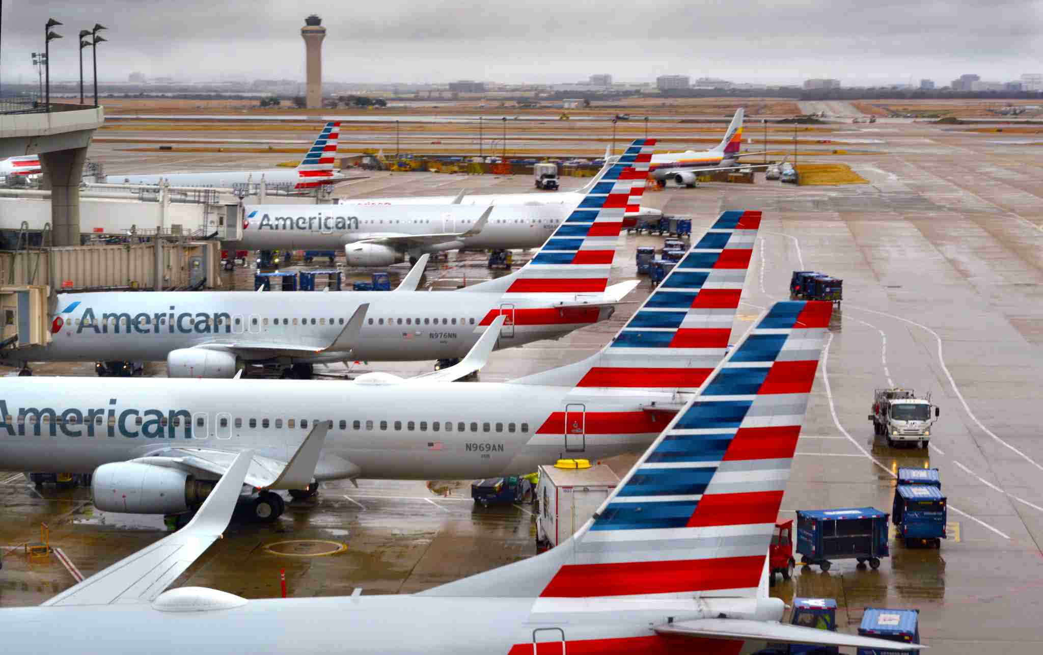 American Airlines passenger jets parked at their gates on a rainy morning at Dallas/Fort Worth International Airport. (Photo by Robert Alexander/Getty Images)