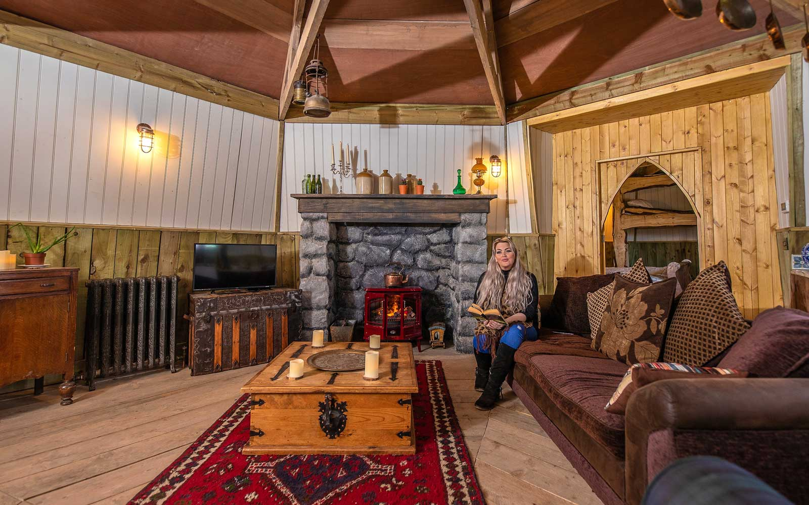 Picture Shows Living Area Holiday home inspired by Harry PotterÕs HagridÕs Hut opens on the North York Moors Harry Potter fans can now rent a holiday cottage inspired by the fictional home of one of the booksÕ main characters, Rubeus Hagrid. The GroundkeeperÕs Cottage has just opened at North Shire near Saltburn on the edge of the North York Moors National Park, inspired by the film portrayal of HagridÕs Hut in the Harry Potter novels. The opening comes just ahead of International Harry Potter Day (2 May). The cottage comprises three interlocking circular slate-roofed buildings, two with turrets, and all with stained glass windows. Guests approach the lantern-lit wooden door before stepping into the spacious open plan living space comprising galley kitchen, dining area, seating in front of a feature fireplace and wood beams festooned with Hagrid-style paraphernalia such as old baskets, ropes, leather bags and lanterns. From the living room one door leads to the circular bedroom complete with double bed and a rustic wooden bunk bed, while a second door opens onto a large bathroom where the star feature is a huge freestanding copper bath. The owner Carol Cavendish, who has been a Harry Potter fan since her early 20s, has also incorporated small touches such as an ink bottle and quill and bespoke copper basin in the bathroom. However whereas Hagrid would have lived relatively frugally, guests staying in GroundkeeperÕs cottage wonÕt have to skimp on lifeÕs luxuries as two comfy sofas in the living room together with sleigh bed and high quality mattresses on the bunk bed make it more of a cosy, comfortable retreat. The cottage, which is available for rent from £195 per night, sleeps up to six (four in the bedroom and two on a sofabed). For those who want to bring their own Fang, one well-behaved dog is also allowed at a small extra cost. This is the next stage in North ShireÕs vision to create a storybook fantasy world for guests. Back i
