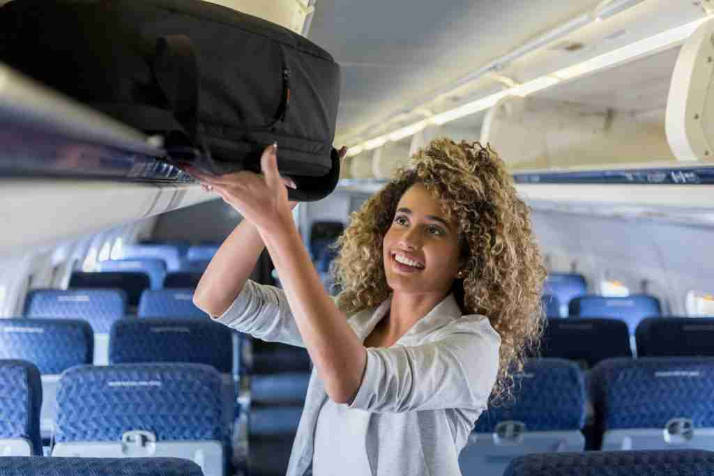 Cheerful young female business traveler places carry on luggage in overhead compartment on airplane.