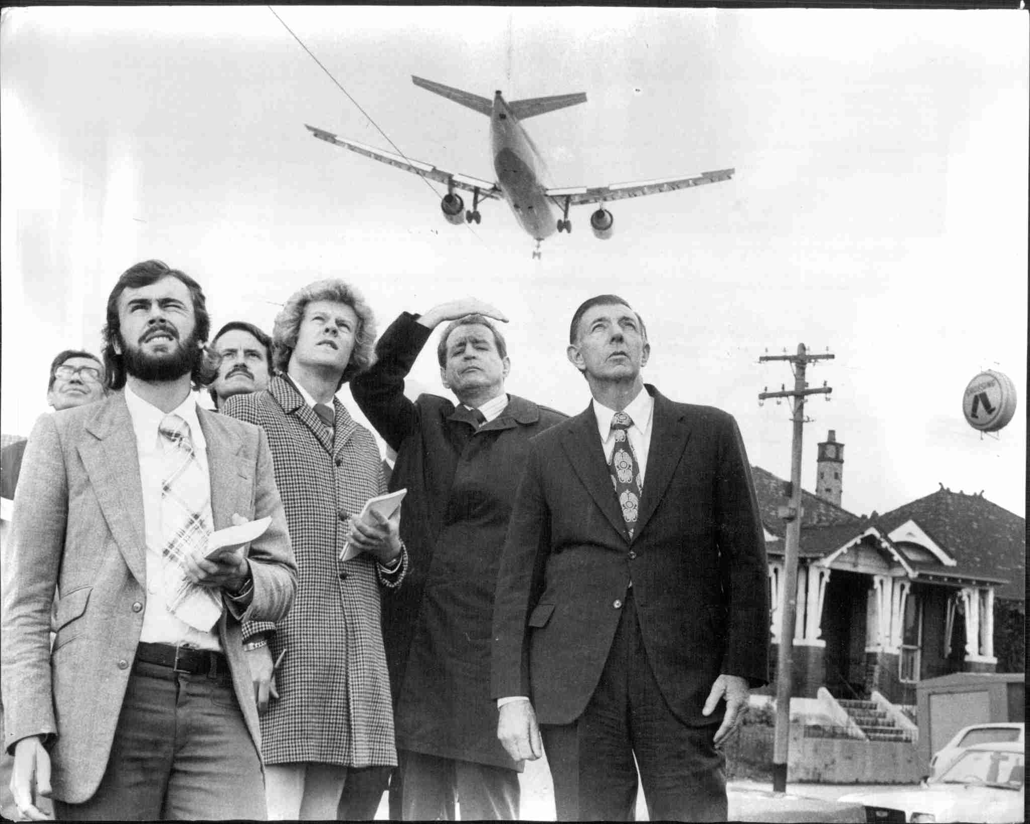 Federal Transport Minister, Charles Jones together with members of the press, Airbus officials and Department of Civil Aviation Officers listen to the noise made by the European A300 Airbus as it lands over the roofs of homes at Sydenham. May 28, 1974. (Photo by Trevor James Robert Dallen/Fairfax Media via Getty Images).