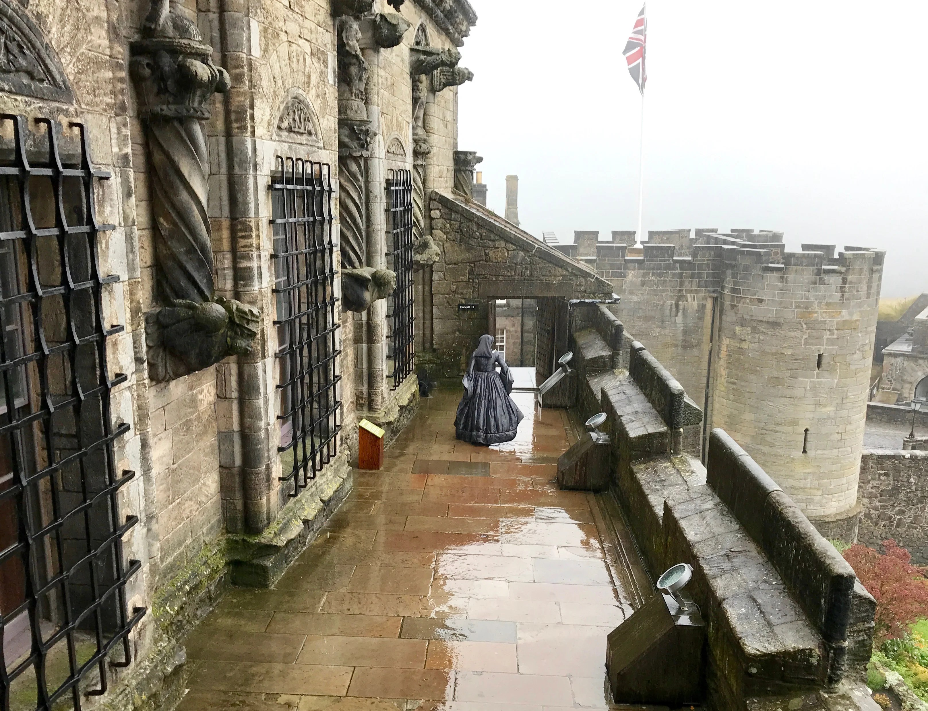 Dressed in period costume, this lady of Stirling Castle walks the ramparts in the rain.