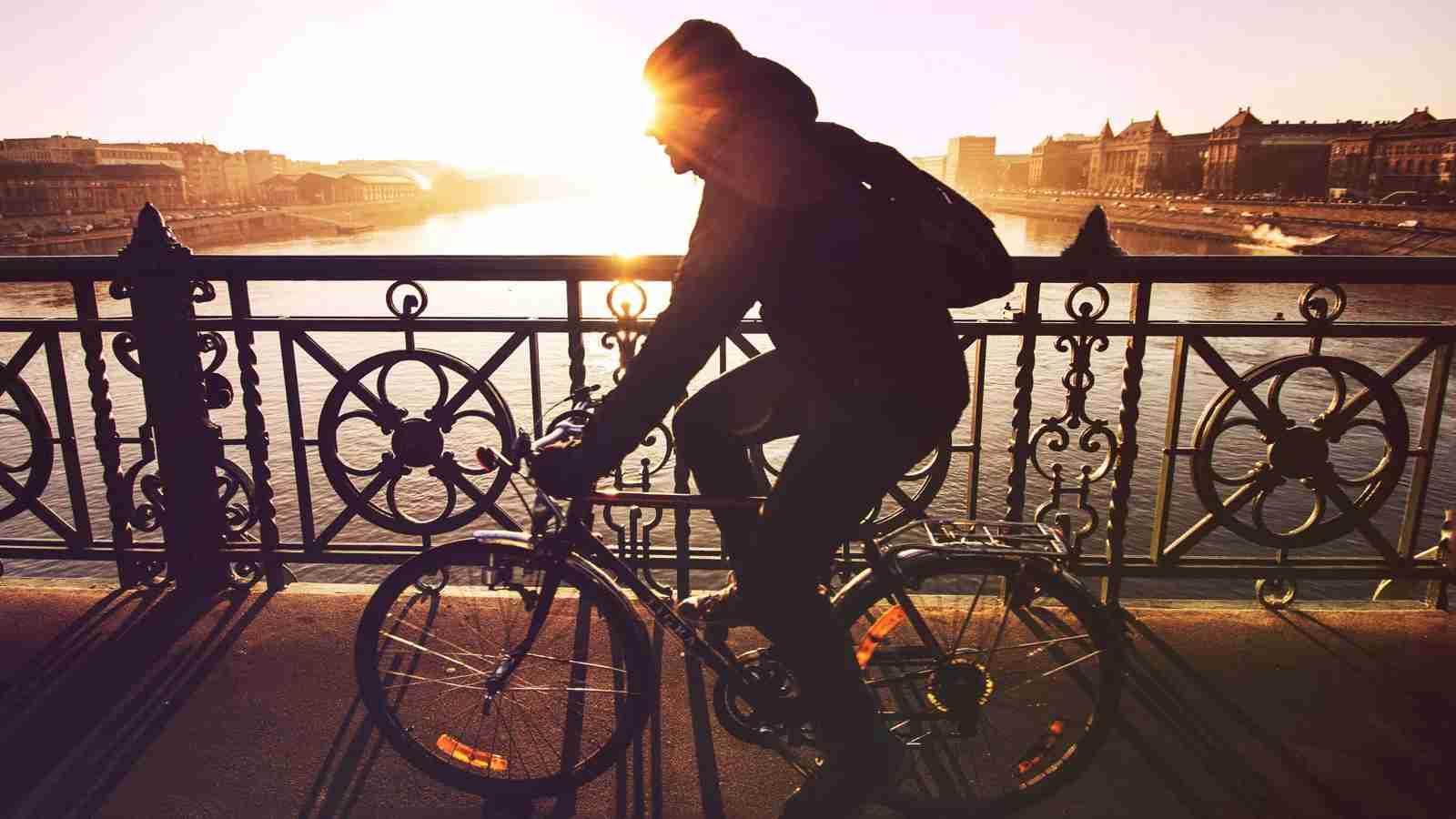 Bike rider on bridge during sunset