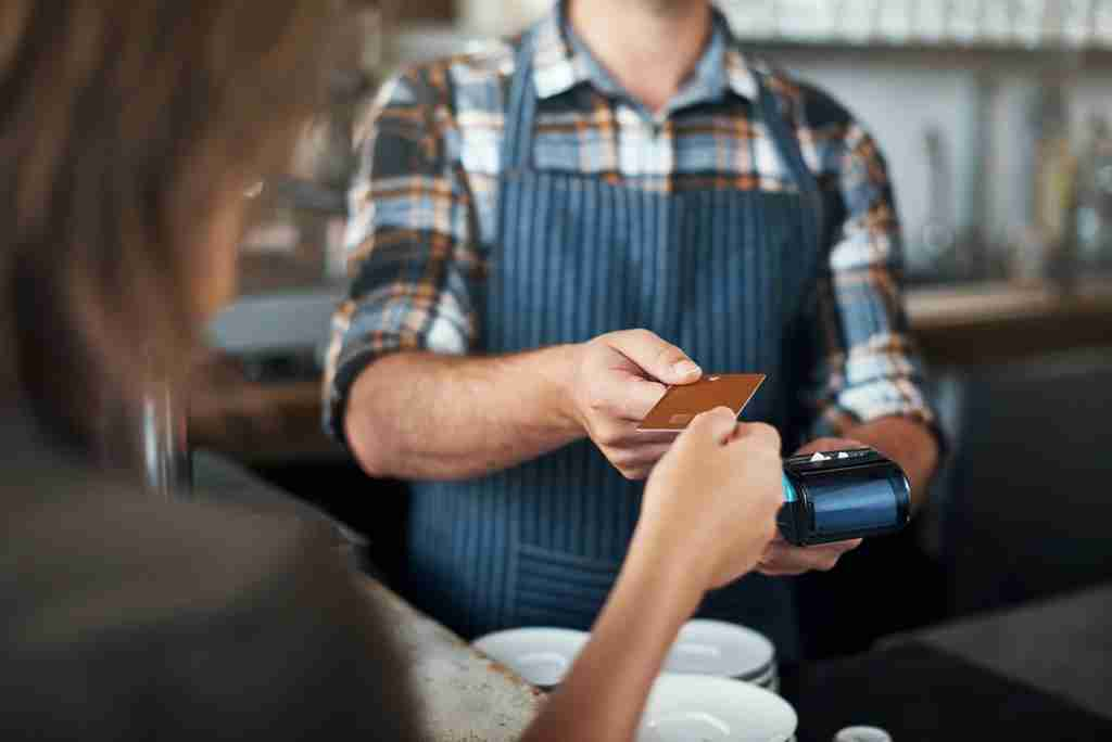 Closeup shot of a unrecognizable person giving a barman a credit card as payment inside of a restaurant(Photo by shapecharge/Getty Images)