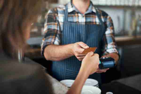 Closeup shot of a unrecognizable person giving a barman a credit card as payment inside of a restaurant (Photo by shapecharge/Getty Images)