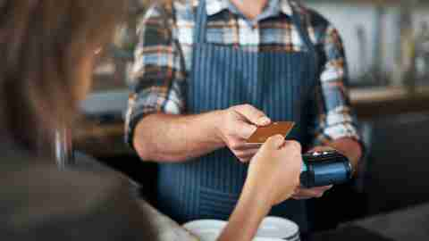 Closeup shot of a unrecognizable person giving a barman a credit card as payment inside of a restaurant