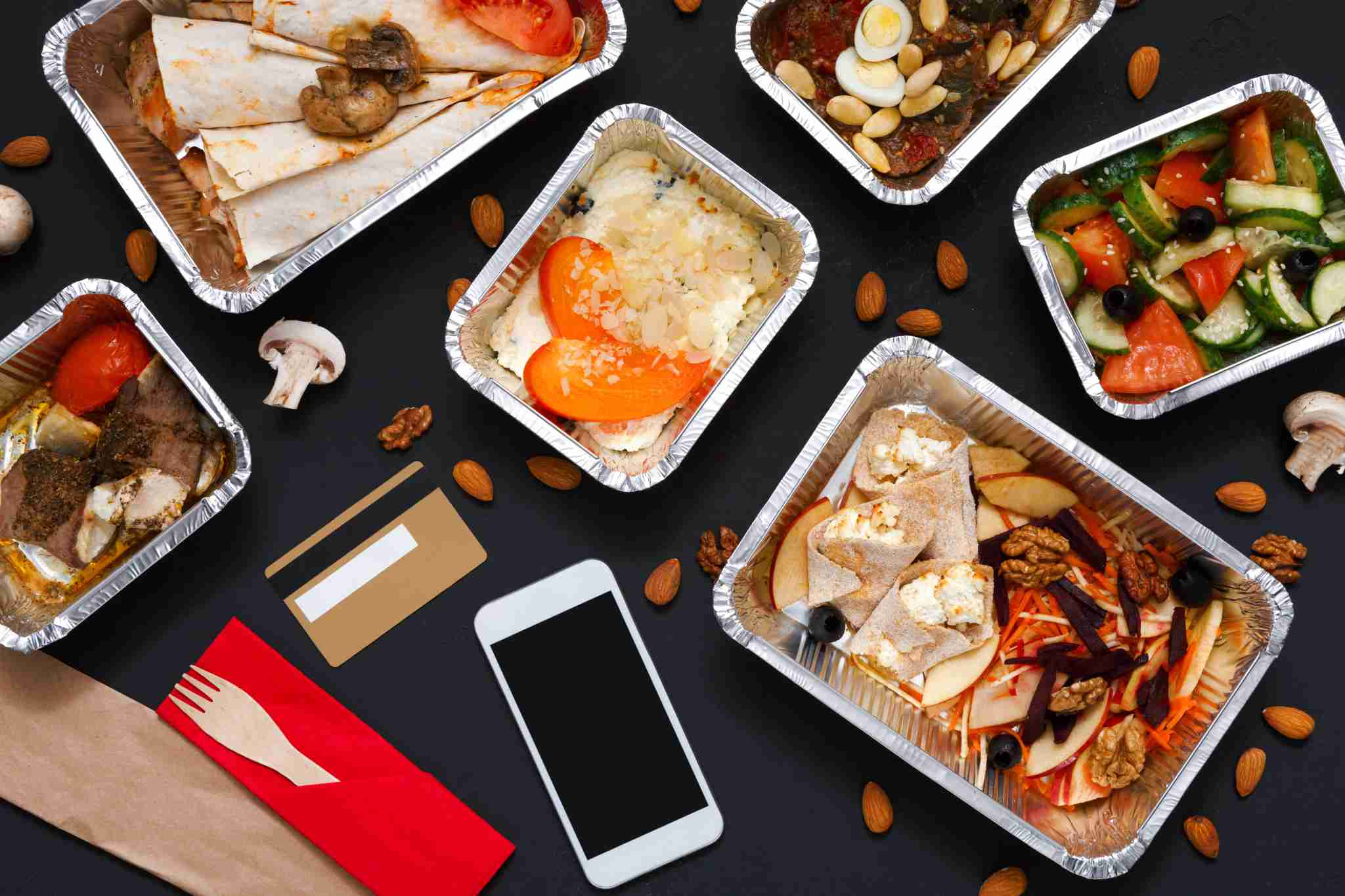 Healthy restaurant food delivery background. Online shopping on smartphone, foil containers with meals on black. Photo by Getty Images