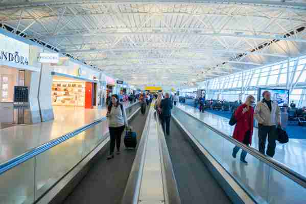 New York, USA - March 29, 2015: People riding the escalator past the row of shops in terminal 1 of the JFK international airport early in the day.