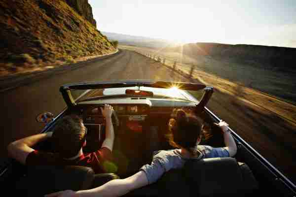 Young couple driving convertible at sunset on desert road (Photo courtesy of Getty Images)