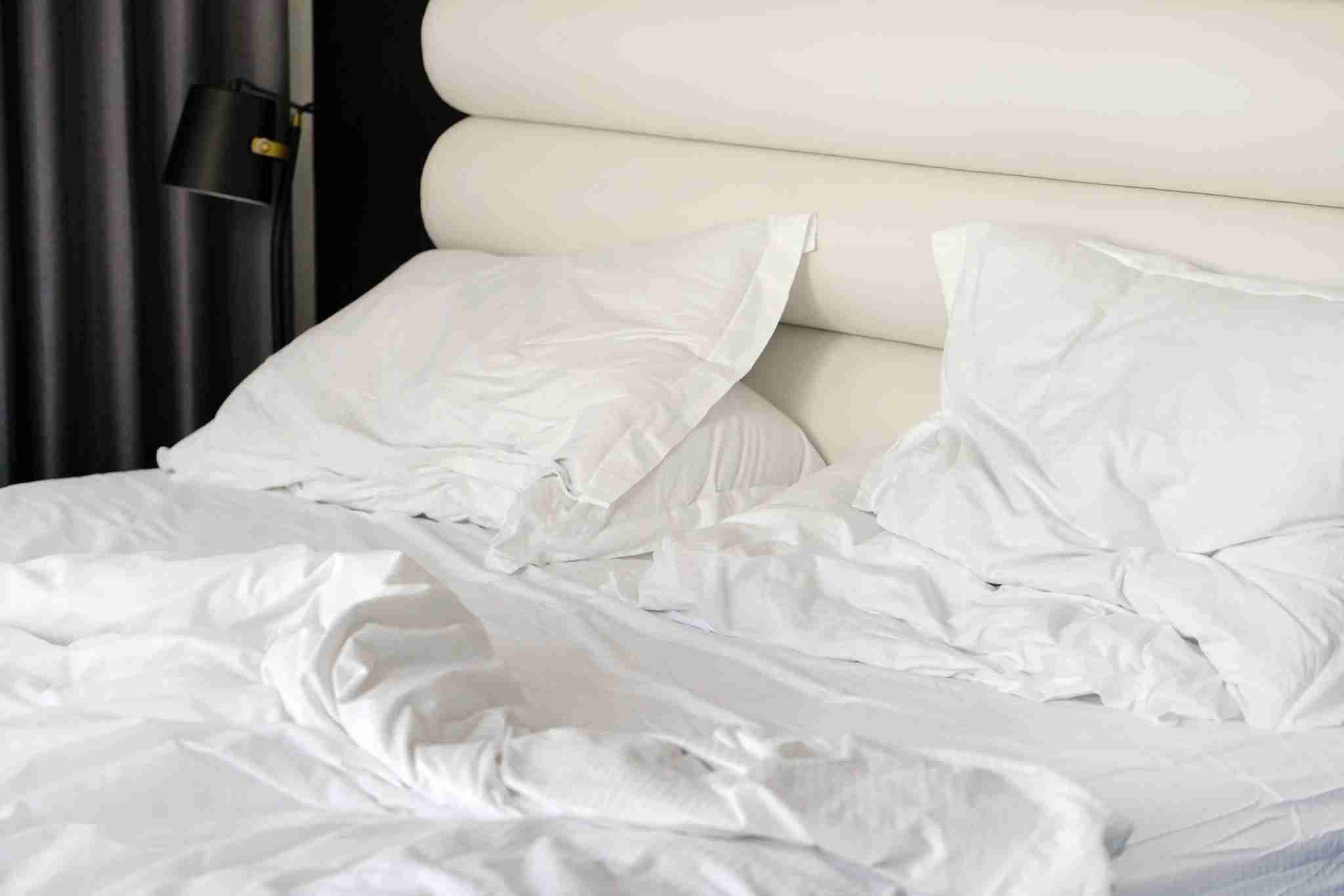 Crumpled bed in the hotel. Close-up of unfinished or messy bed after funny night, sex of new married couple. Dirty bed with decorate room. Used linens, bed sheet and pillows messed up. Igor Vershinsky / Getty Images.