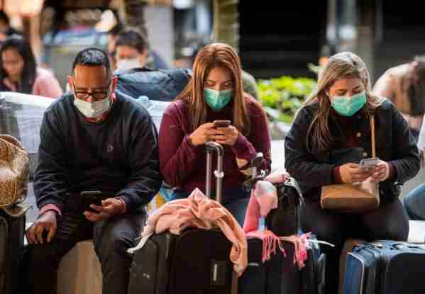 Passengers wear face masks to protect against the spread of the Coronavirus as they arrive on a flight from Asia at Los Angeles International Airport, California, on January 29, 2020. - A new virus that has killed more than one hundred people, infected thousands and has already reached the US could mutate and spread, China warned, as authorities urged people to steer clear of Wuhan, the city at the heart of the outbreak. (Photo by Mark RALSTON / AFP) (Photo by MARK RALSTON/AFP via Getty Images)