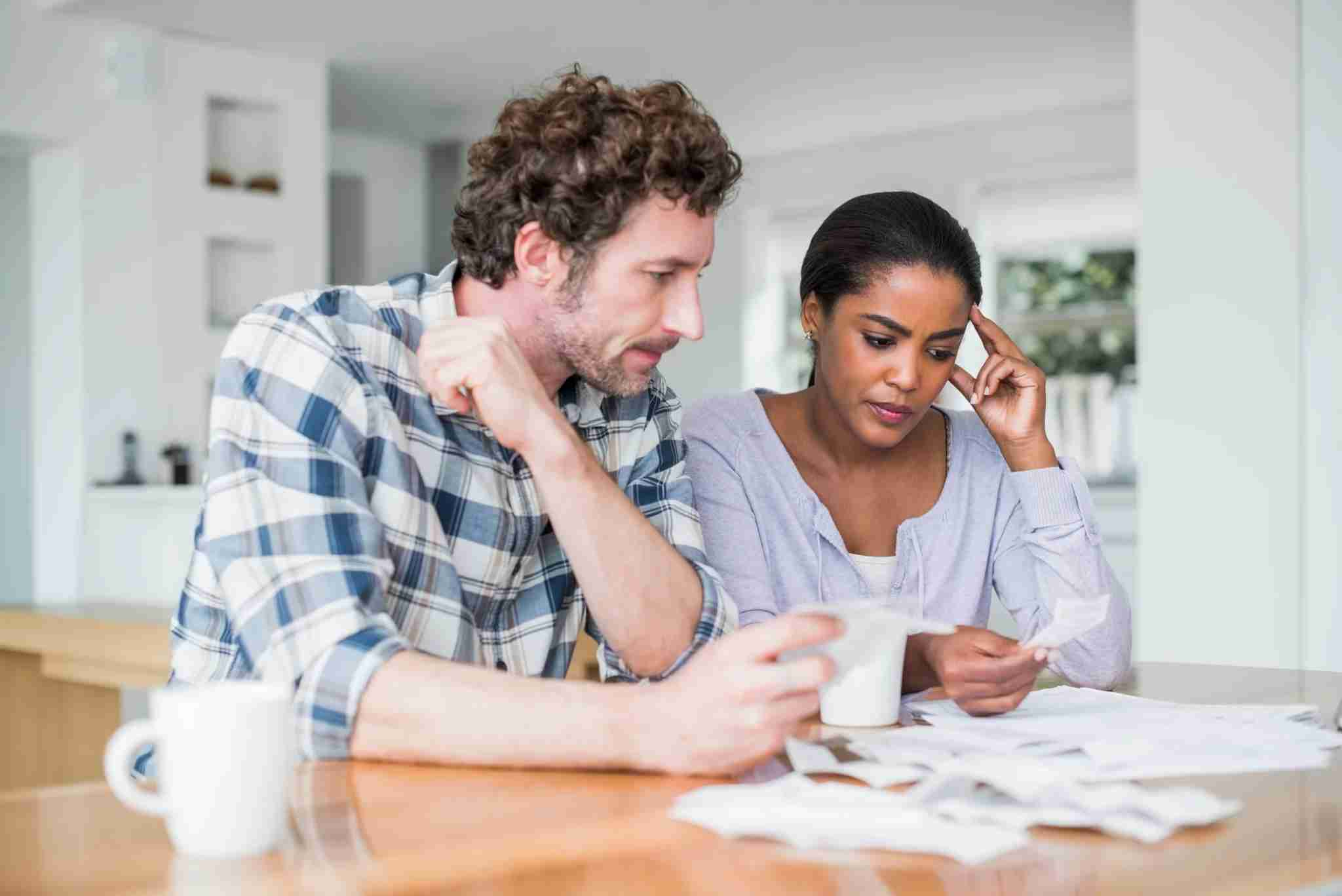 Tensed multi-ethnic couple reading bills at home. (Photo by Portra/Getty)