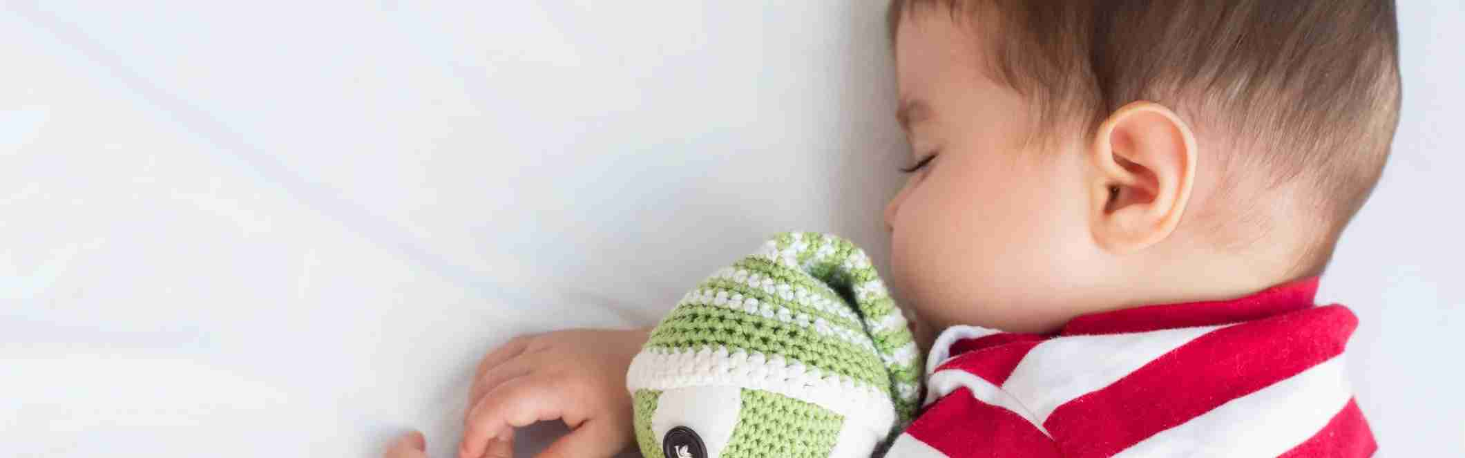 Baby sleeping in the crib with a crochet doll