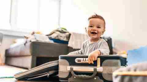 baby playing in suitcase
