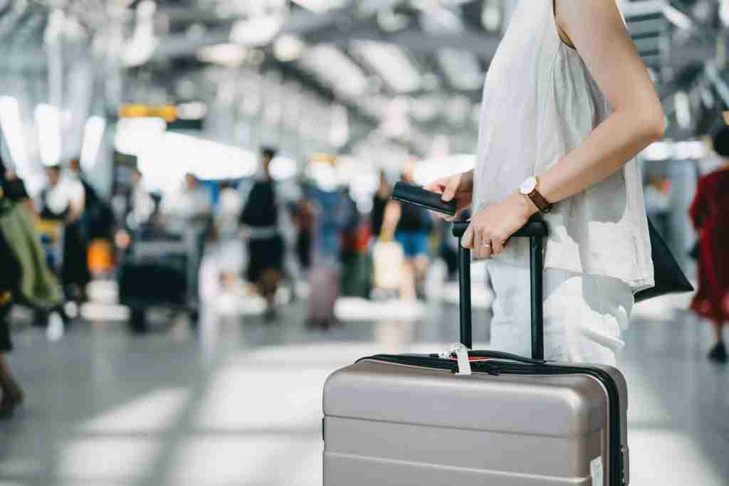 Cropped image of young woman holding passport and suitcase walking in the international airport hall. d3sign/Getty