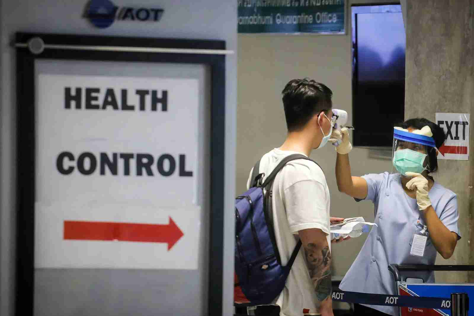 A health official checks the temperature of an incoming passenger during a health assessment at an airport checkpoint. (Photo by VIVEK PRAKASH/AFP/Getty Images)