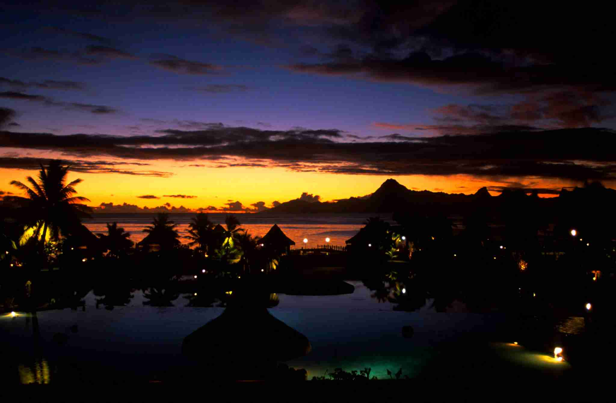 FRENCH POLYNESIA - 2002/01/01: French Polynesia, Society Islands, Tahiti, Beachcomber Hotel, After Sunset, Pool, Morea In Background. (Photo by Wolfgang Kaehler/LightRocket via Getty Images)