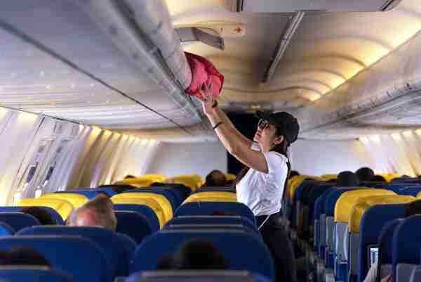 Person Putting Luggage into Overhead Bin