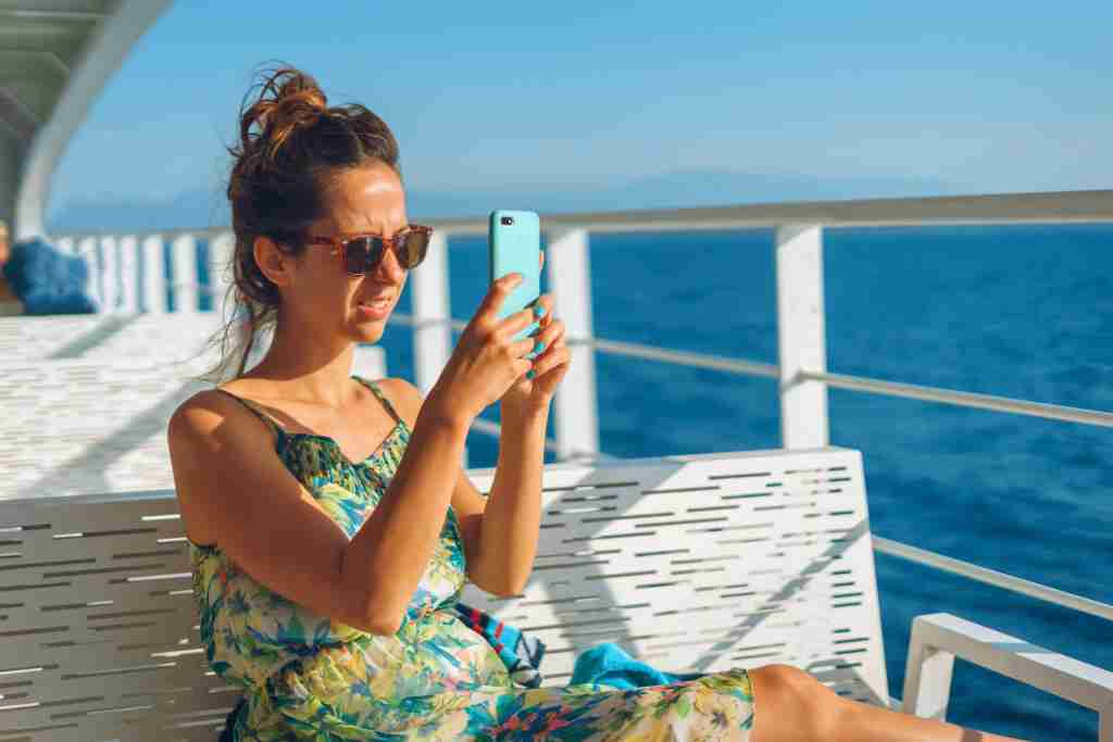 Young woman on the bench on deck of the ferry boat or ship yacht taking photos pictures using her smart mobile phone while sailing on the vacation in sunny day