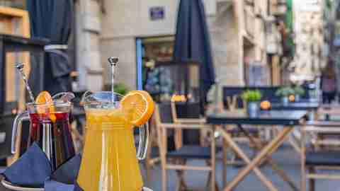 A jug of orange juice and other of Sangria on the table in an outdoor restaurant in Valencia, Spain