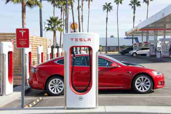Red Tesla Charging at a Supercharger