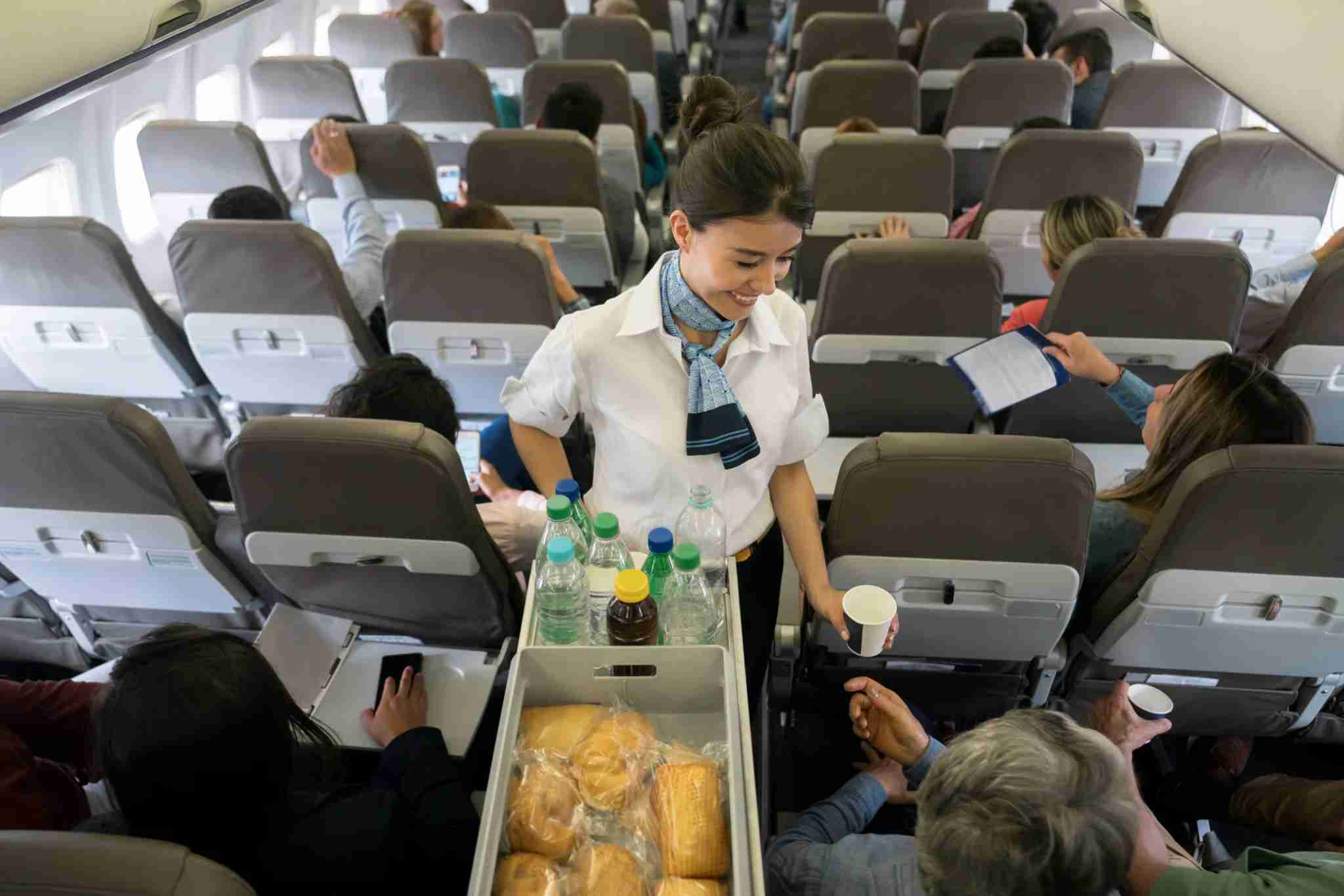 Portrait of a friendly air hostess serving food and drinks onboard and smiling - travel concepts
