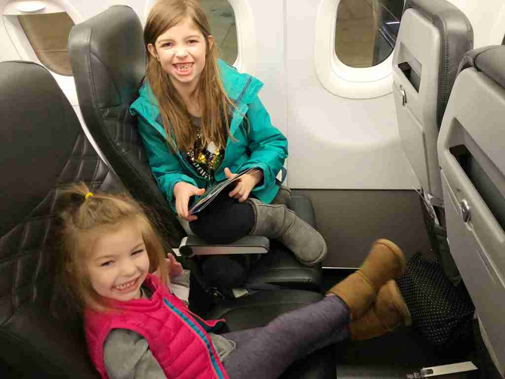 My girls enjoying extra legroom seats on Frontier Airlines