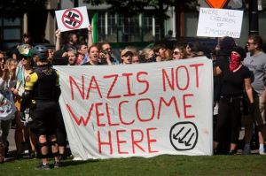 EDITORS NOTE: Graphic content / Antifa members hold a sign denouncing Nazis along a road at a waterfront park in downtown Portland, Oregon September 10. 2017. .Several hundred protesters descended in to downtown Portland to oppose the right-wing group. / AFP PHOTO / Natalie Behring (Photo credit should read NATALIE BEHRING/AFP/Getty Images)