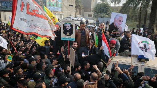 """Supporters of the Hashed al-Shaabi paramilitary force attend the funeral procession of Iraqi paramilitary chief Abu Mahdi al-Muhandis, Iranian military commander Qasem Soleimani, and eight others in the capital Baghdad's district of al-Jadriya, near the high-security Green Zone, on January 4, 2020. - Thousands of Iraqis chanting """"Death to America"""" joined the funeral procession for Iranian military commander Qasem Soleimani and Muhandis, both killed in a US air strike. The cortege set off around Kadhimiya, a Shiite pilgrimage district of Baghdad, before heading to the Green Zone government and diplomatic district where a state funeral was to be held attended by top dignitaries. In all, 10 people -- five Iraqis and five Iranians -- were killed in Friday morning's US strike on their motorcade just outside Baghdad airport. (Photo by AHMAD AL-RUBAYE / AFP) (Photo by AHMAD AL-RUBAYE/AFP via Getty Images)"""