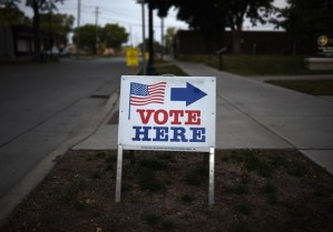 """MINNEAPOLIS, MN - AUGUST 14: A sign reading """"Vote Here"""" points toward a polling place for the 2018 Minnesota primary election at Holy Trinity Lutheran Church on August 14, 2018 in Minneapolis, Minnesota. (Photo by Stephen Maturen/Getty Images)"""