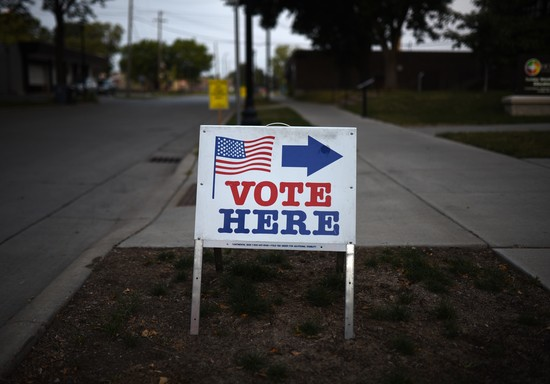 "MINNEAPOLIS, MN - AUGUST 14: A sign reading ""Vote Here"" points toward a polling place for the 2018 Minnesota primary election at Holy Trinity Lutheran Church on August 14, 2018 in Minneapolis, Minnesota. (Photo by Stephen Maturen/Getty Images)"