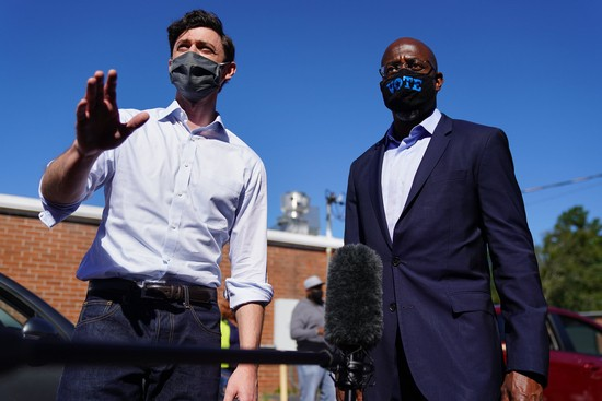 LITHONIA, GA - OCTOBER 03: Democratic U.S. Senate candidates Jon Ossoff and Rev. Raphael Warnock hand out lawn signs at a campaign event on October 3, 2020 in Lithonia, Georgia. The two are hoping to unseat incumbent Senators David Perdue and Kelly Loeffler. (Photo by Elijah Nouvelage/Getty Images)