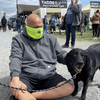 John Fetterman sits next to and pets Lance the Weed Dog at the cannabis festival.