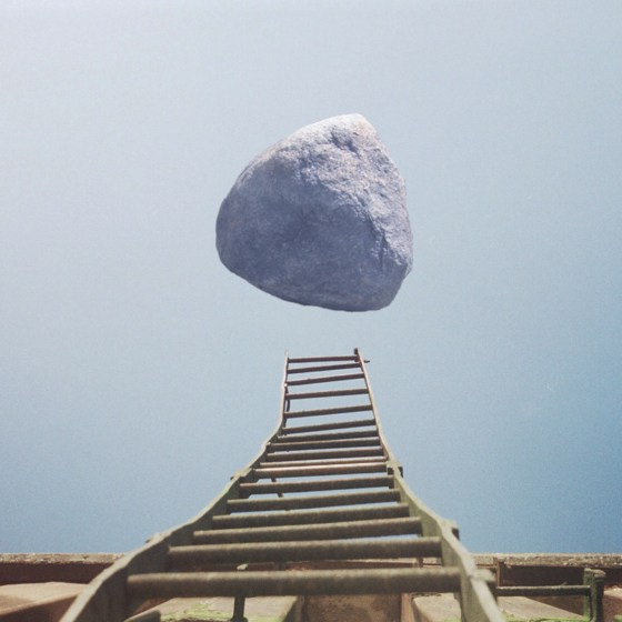 A boulder hovers above a ladder in a dreamscape