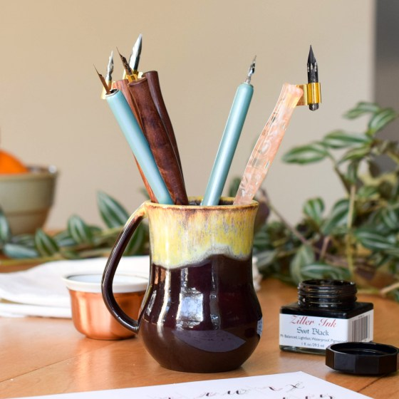 This pen holder or art water cup comes in two colors: brown with a turquoise drip glaze, or brown with a yellow drip glaze.