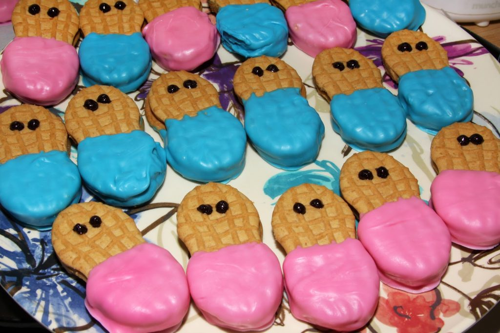 nutter butters dipped in pink and blue frosting for gender reveal