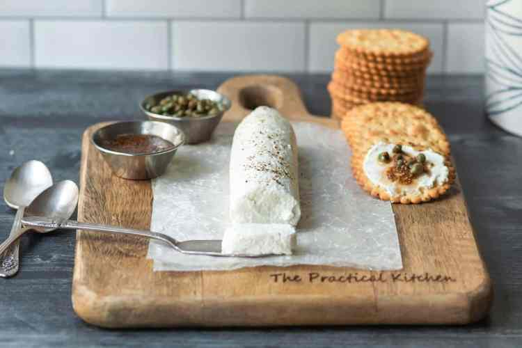 a log of coat cheese in the middle of a wooden board. a slice has been cut off the front of the log. small bowls of capers and mustard are to the left. a stack of crackers is to the right.