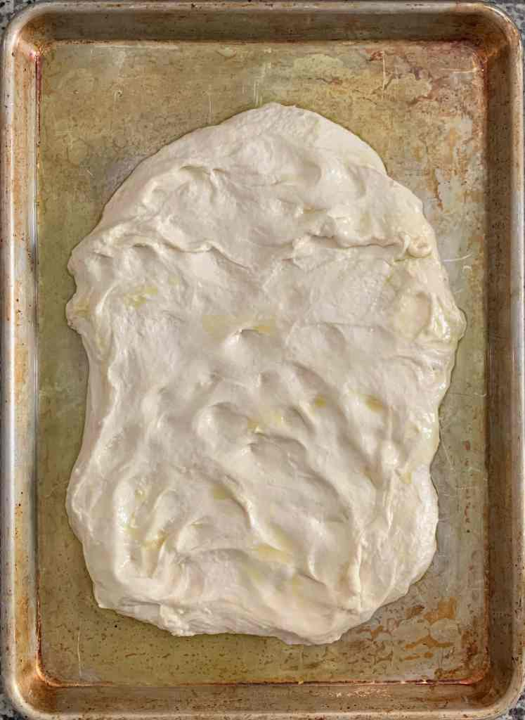 An overhead shot of focaccia dough in a sheet pan. The dough has been loosely flattened and stretched. It doesn't quite reach the edges of the pan.