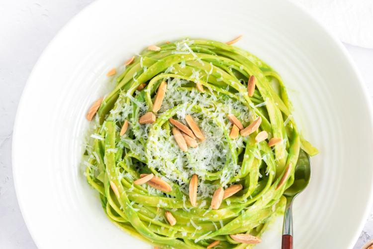 an overhead shot of fettuccini pasta coated in green spaghetti sauce in the center of a shallow white bowl topped with parmesan and toasted almond slivers