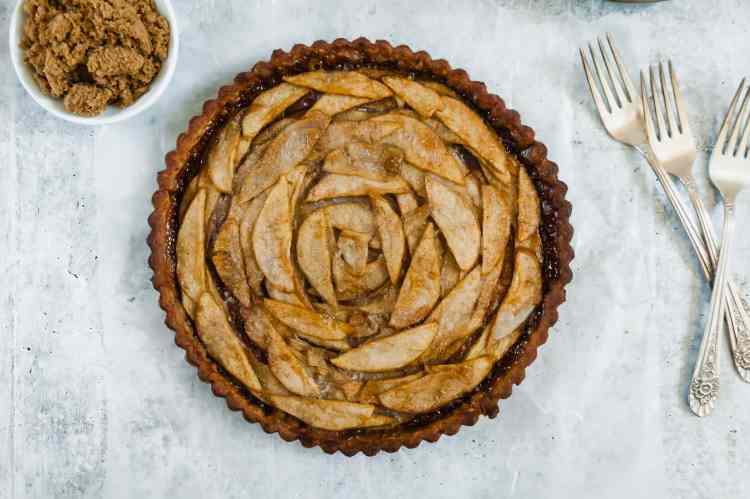 a pear and gruyere tart sits on a grey concrete counter. a small bowl of brown sugar is to its left, and three forks sit to its right.