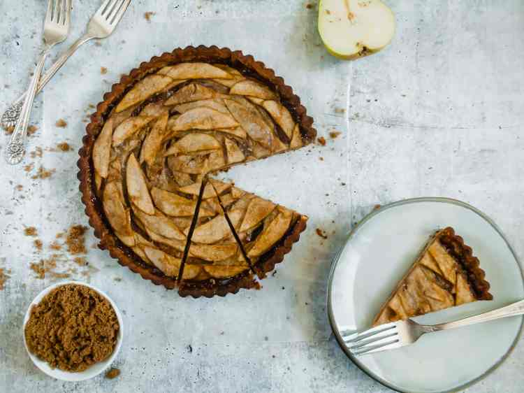 a tart with three slices cut out of the bottom right. one slice is on a small plate with a fork. half a pear is visible at the top of the image, and two forks and a small bowl of brown sugar are to the left of the tart.