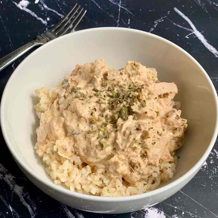 a bowl of tuna newberg served over rice and garnished with dried oregano. the coziest thing you can eat in an emergency.